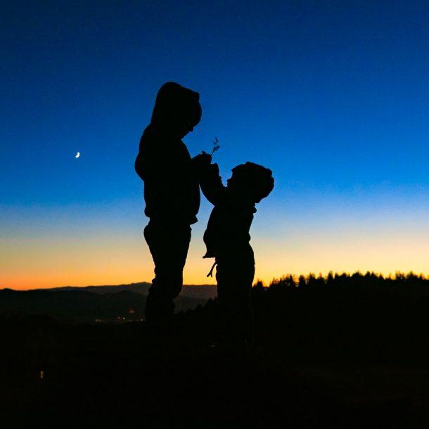 Kind fotografieren lernen - Zwei Kinder halten beim Sonnenuntergang etwas in der Hand - Silhuette